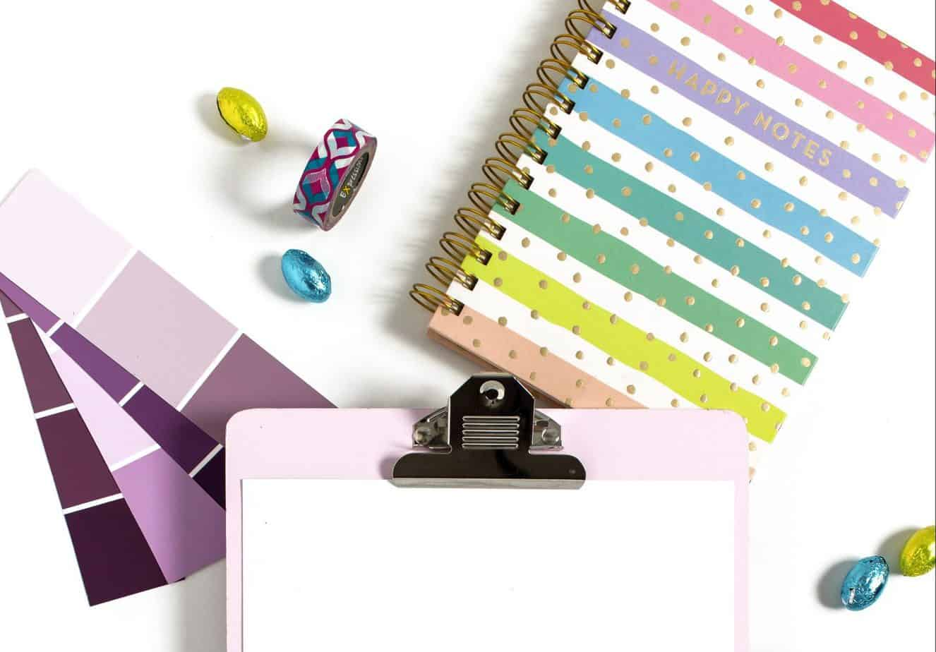 Clip board with colorful objects around it