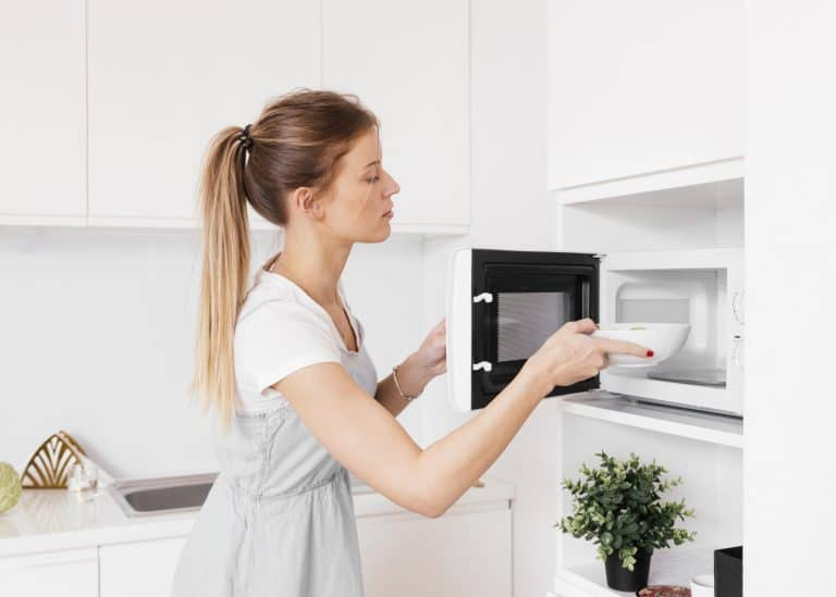 Women putting bowl in microwave