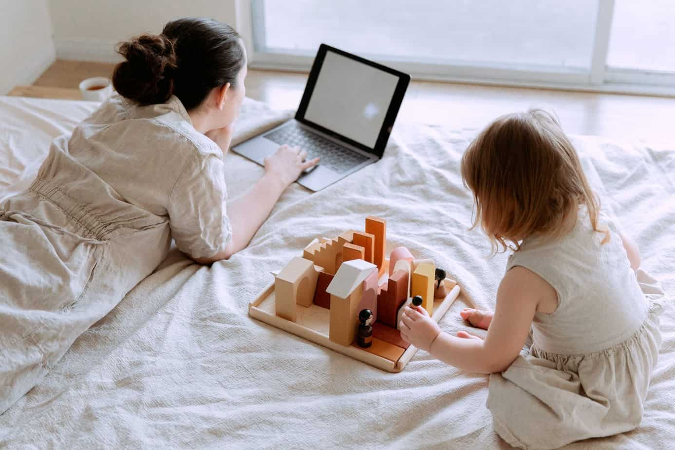 young woman lying on bed and using laptop while daughter playing with wooden constructor