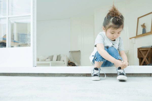 child putting their shoes on independently