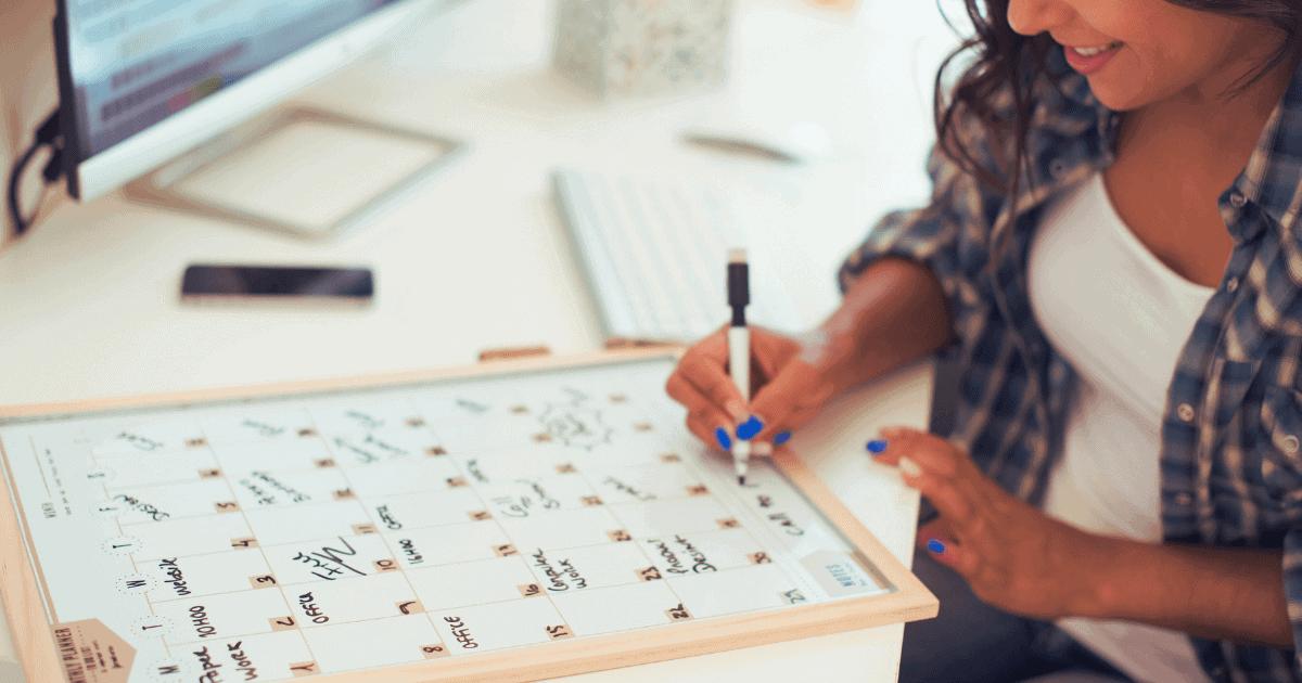 Women writing on erasable calendar